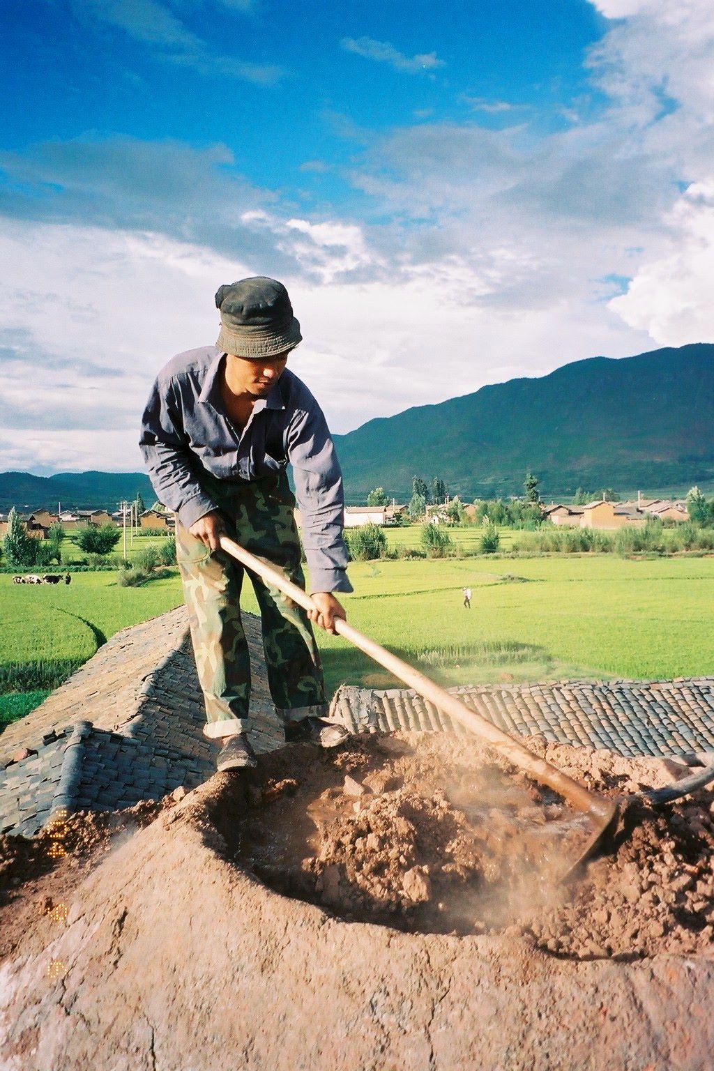 雲南省。だるま窯の温度調整。
